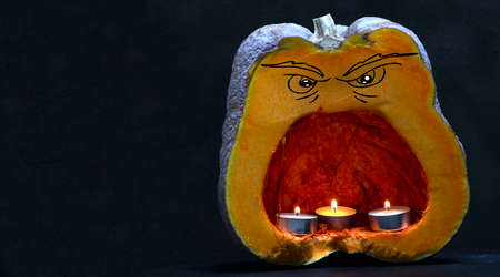 pumpkin with evil face with open mouth and candles inside. concept for halloween decorations