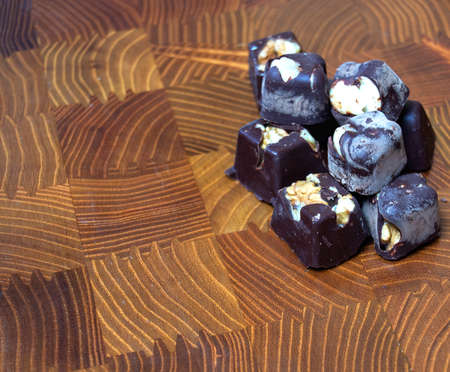 dark chocolates with almonds and nuts on a wooden chopping board