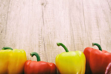 wooden surface: yellow and red peppers on a wooden surface