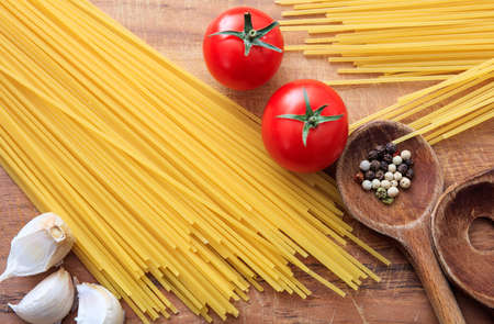 ladles: Raw spagetti pasta with tomatoes, garlic and wooden ladles