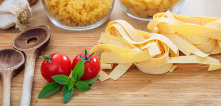 ladles: Raw pappardelle pasta with tomatoes, garlic and wooden ladles Stock Photo