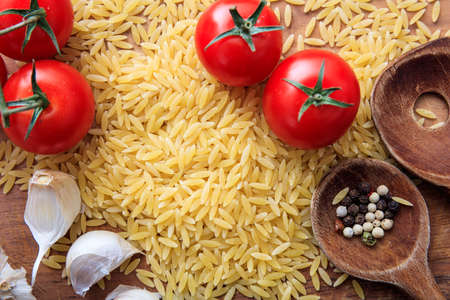 ladles: Raw orzo pasta with tomatoes, garlic and wooden ladles