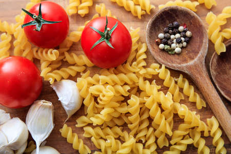 ladles: Raw fusilli pasta with tomatoes, garlic and wooden ladles