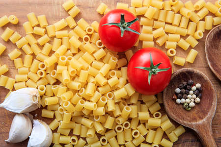 ladles: Raw macaroni pasta with tomatoes, garlic and wooden ladles