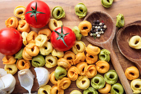ladles: Raw tortellini pasta with tomatoes, garlic and wooden ladles Stock Photo