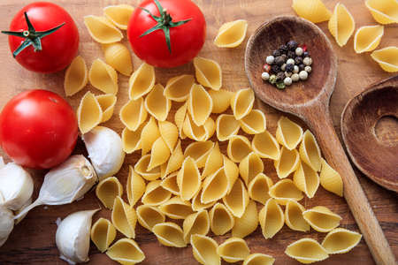 ladles: Raw shells pasta with tomatoes, garlic and wooden ladles Stock Photo