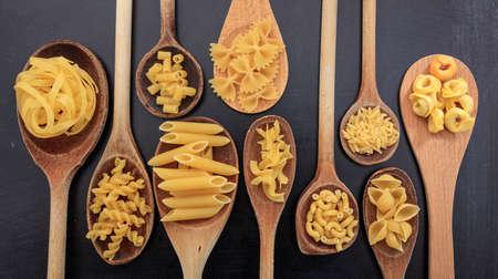 ladles: Various shapes of pasta on ladles, black background