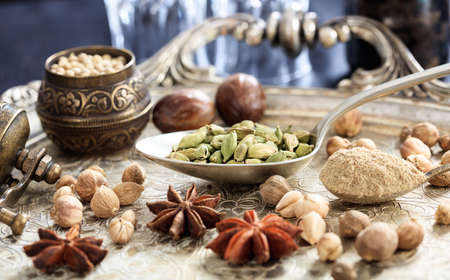 Cardamom seeds and powder in spoons Stock Photo