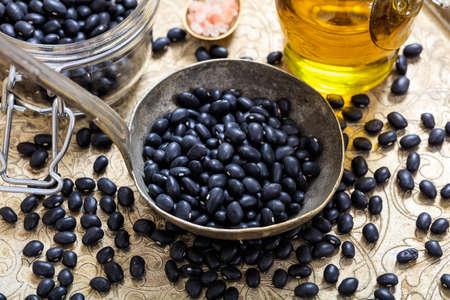 black metallic background: Raw black beans background and a metallic ladle