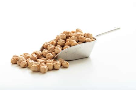 legumbres secas: garbanzos crudos en un metálica primicia sobre fondo blanco Foto de archivo