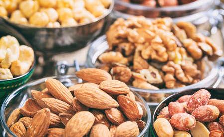 Amandelen, pindakaas en andere noten in kommen Stockfoto