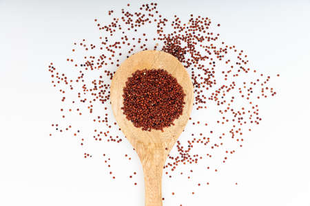 red quinoa: Red quinoa in a wooden spoon on white background