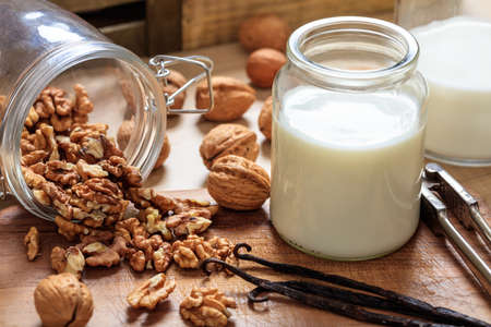 Vegan milk from walnuts on a wooden surface Stock Photo