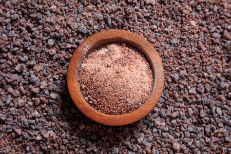 Wooden bowl on black indian salt background
