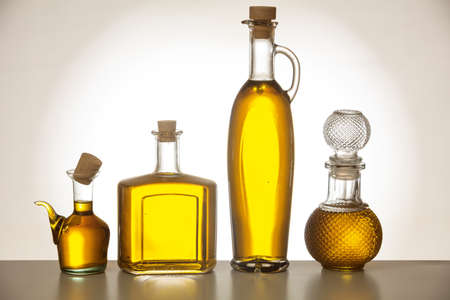 Set of glass bottles with olive oil on gradient background