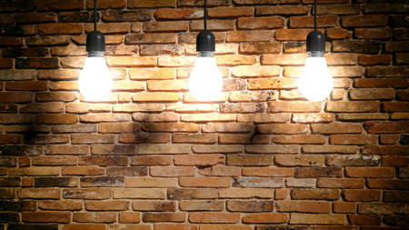 3d rendering light bulbs hanging on brick wall background Stock Photo