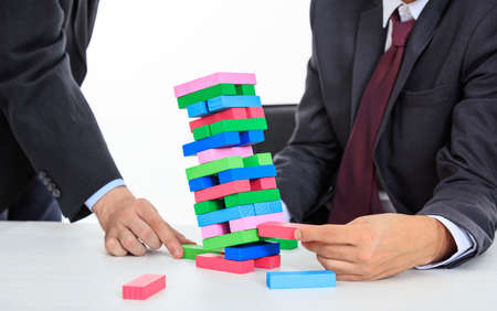 Businessmen playing colorful wooden blocks game Zdjęcie Seryjne