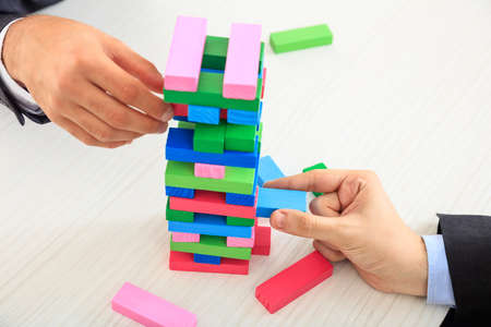 Hands playing wooden blocks game