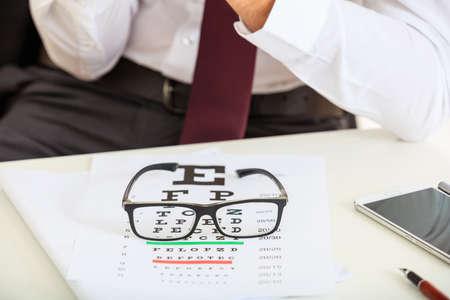 examen de la vista: examen de la vista del ojo y un par de gafas en un escritorio Foto de archivo