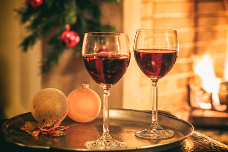 Two glasses of red wine near a fireplace