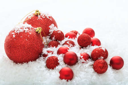 Red christmas balls and snow on white background