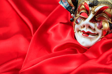 harlequin: Harlequin carnival mask isolated on red satin background