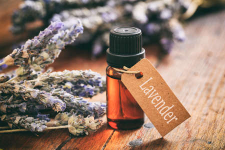 Lavender bunch and essential oil on wooden background Stockfoto