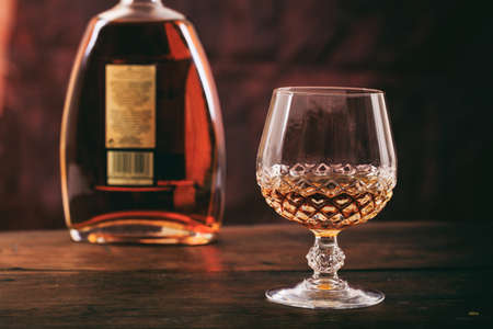 Bottle and crystal glass of cognac on a wooden table