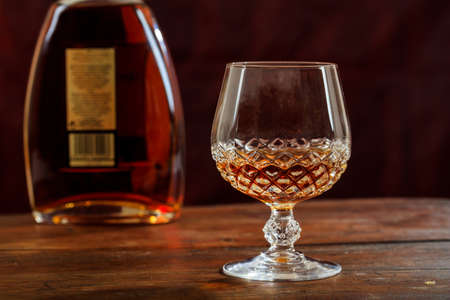 crystal glass: Bottle and crystal glass of cognac on a wooden table