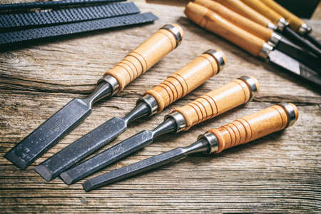 Set of old chisels on a wooden background