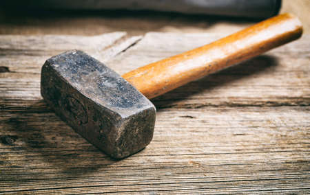 Old used hammer on a wooden table
