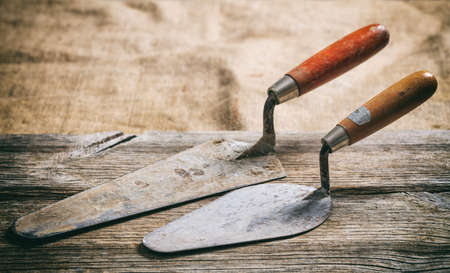 Old used trowels on a wooden table