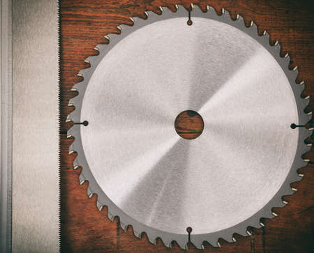 Metal saw blade on a wooden background