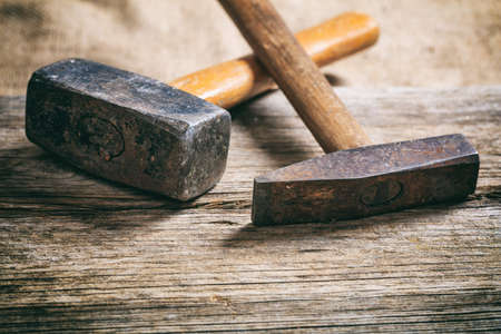 Two olld hammers on a wooden table