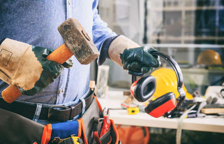 Worker with a tool belt holding a hammer and earphones Stock Photo
