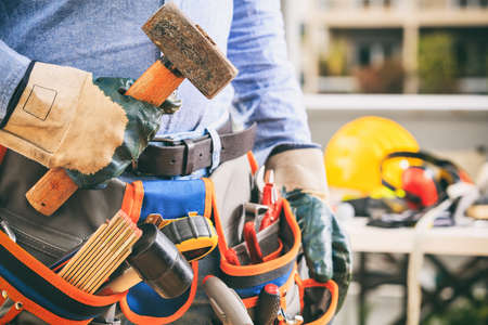 Worker with a tool belt holding a hammer