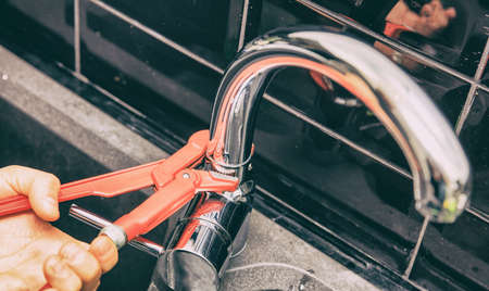 Hand of person tightening up a screw on a tap. Horizontal indoors shot.