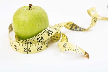 metro de medir: Green apple and measuring tape on white background