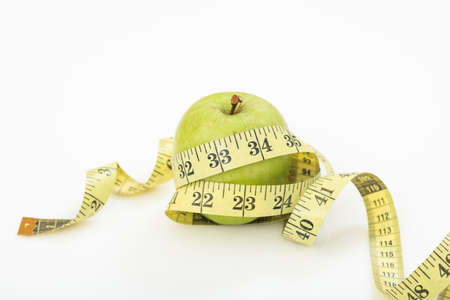 Green apple and measuring tape on white background