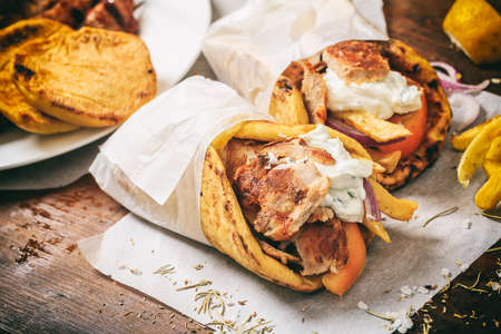 Greek gyros wraped in a pita bread on a wooden background Stok Fotoğraf