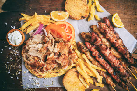Greek gyros dish and meat skewers on a wooden background