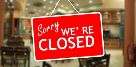 Sorry we zijn gesloten teken opknoping op een glas storefront Stockfoto