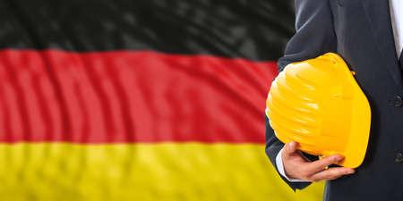 Ingenieur op een afzwijnende vlagachtergrond van Duitsland. 3D illustratie Stockfoto
