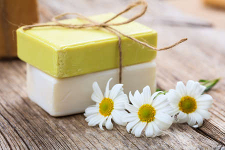 Natural handmade soap bars and chamomile on wooden background Imagens - 74163349