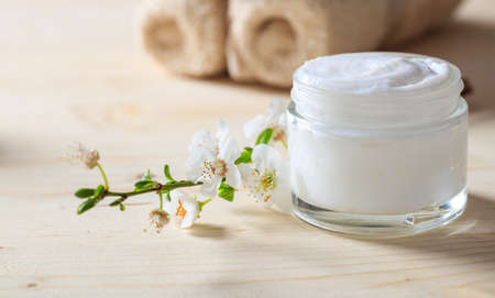 Moisturizing cream and almond blossoms on wooden background