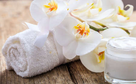Moisturizing cream and white orchid on wooden background