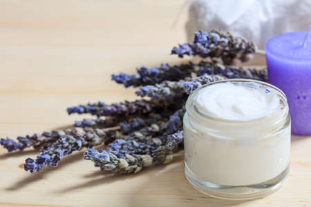 Moisturizing cream and lavender on wooden background