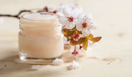 Moisturizing cream and cherry blossoms on wooden background