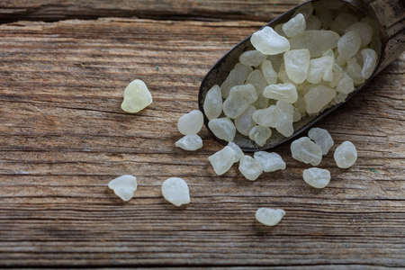 masticate: Chios mastic tears in a scoop on a wooden background