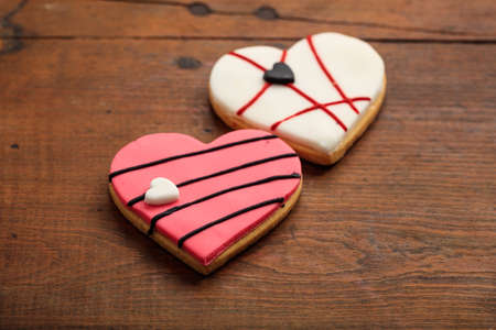 gingerbread: Two heart shaped biscuits on wooden background Stock Photo